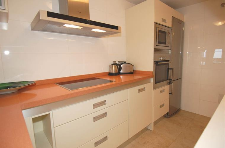 Clean fully-fitted kitchen with polished marble worktops.