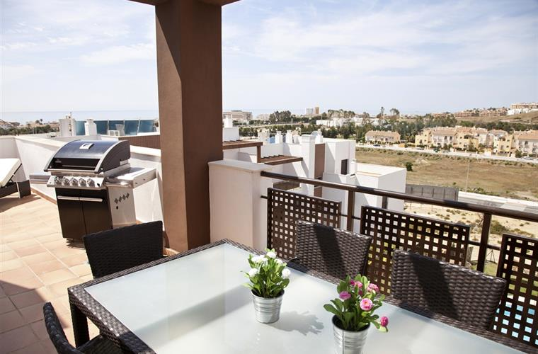The terrace extends around the apartment, facing towards the sea