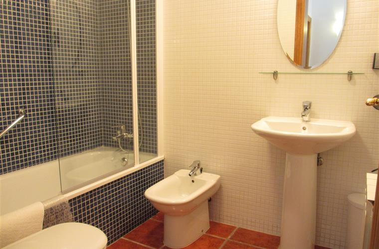 Blue bathroom with bath, toilet, bidet, hairdryer