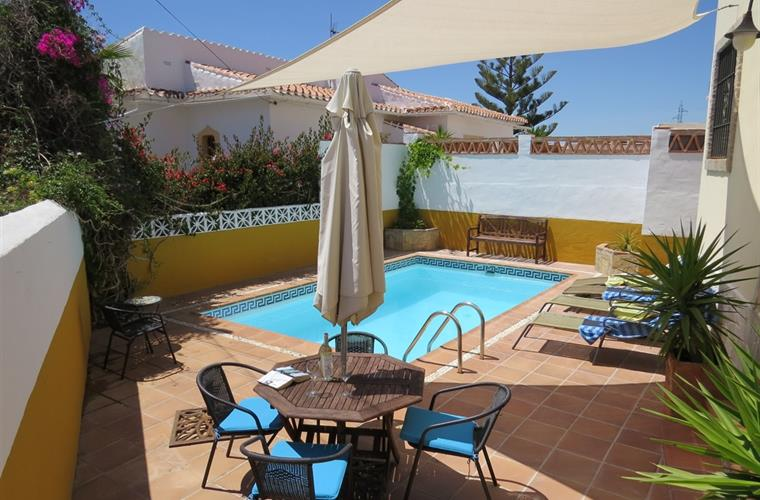 Pool terrace with outdoor dining and sun lounges