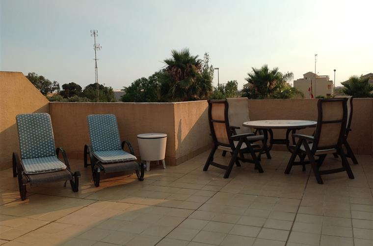 The terrace with dining table, sunbeds and BBQ