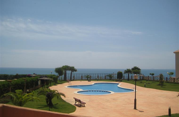 View of communal pool and sea in foreground