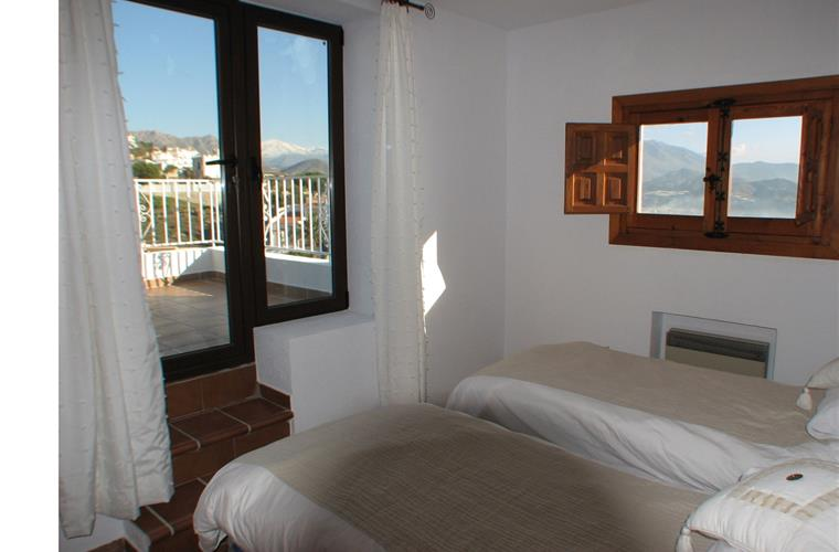 The twin-bedded room upstairs has a terrace with mountain views