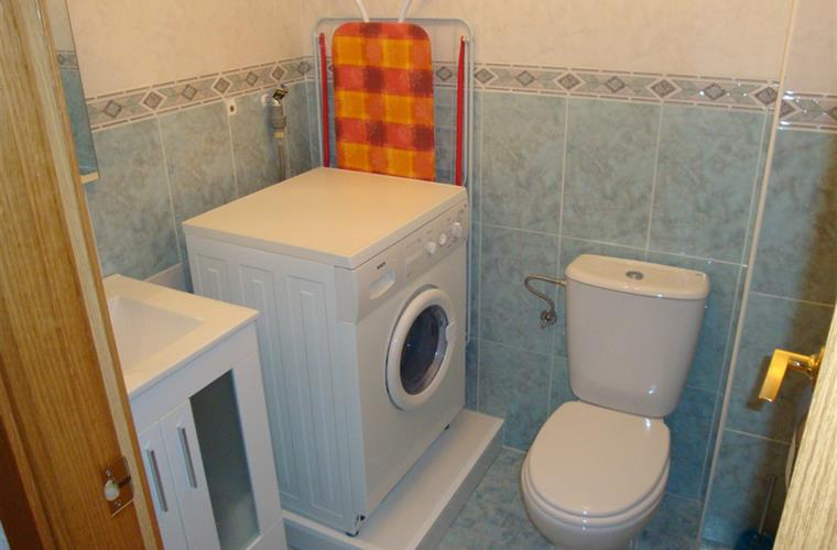 Separate toilet room with sink and washing machine.