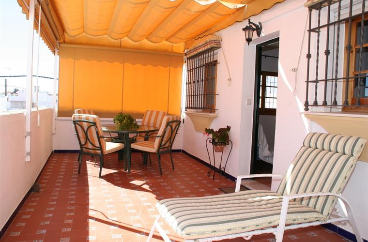Extensive private terrace with awning and outdoor furniture.