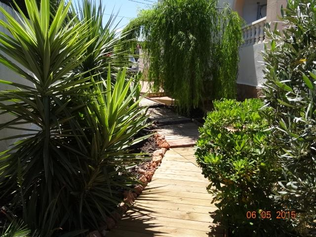 Wooden decking pathway right through all rear garden
