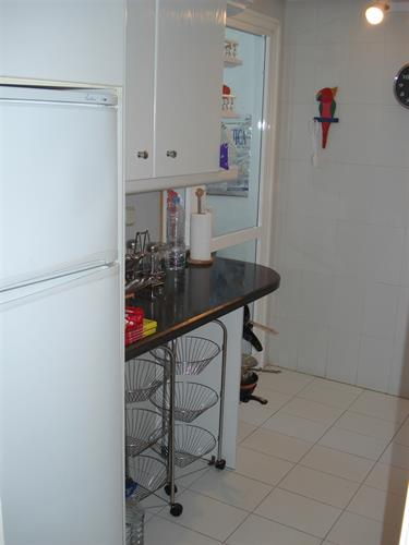 View of the fridge, granite worktop and utility room to left