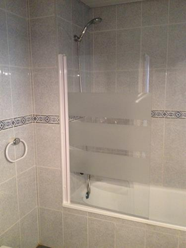 Shower over bath with solid glass shower screen