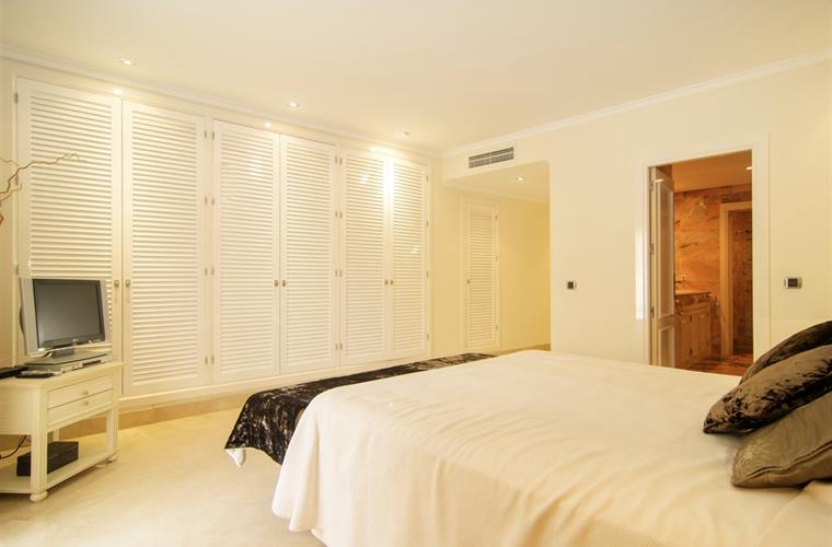 Master bedroom with large wardrobes and TV