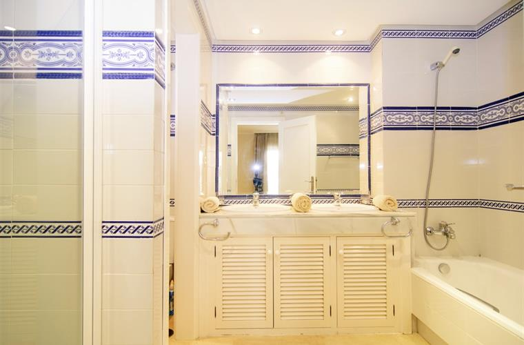 En suite bathroom with bathtub and separate shower