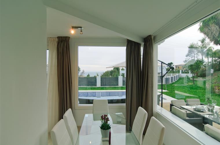 Dining area in living room with views of garden, terrace and pool