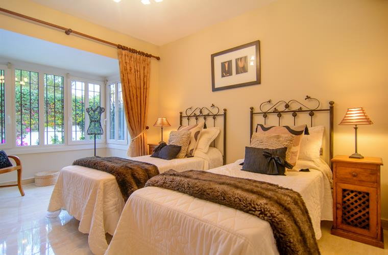 Guest bedroom with two single beds, large windows