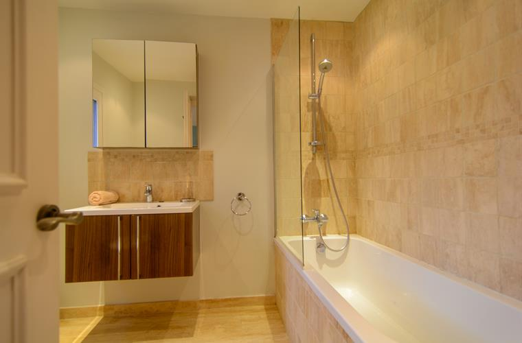 En suite bathroom with bathtub with shower