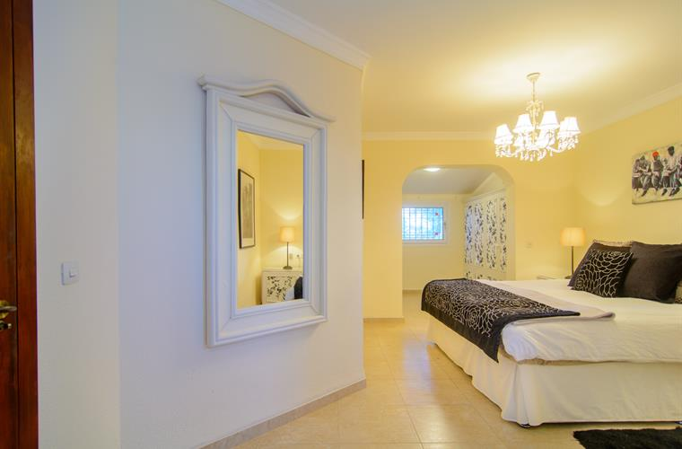 Master bedroom with double bed and mirror