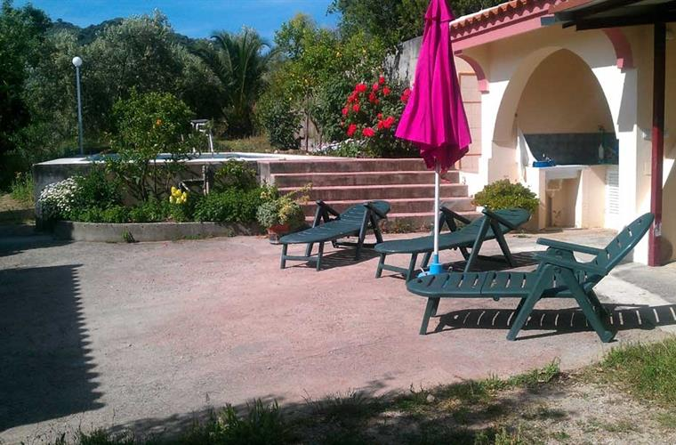 Sun loungers in front of the steps up to the pool & BBQ right