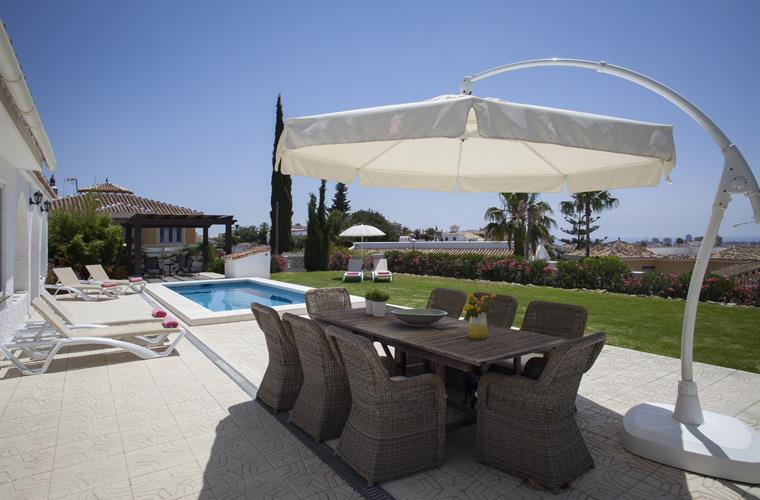 The big parasol easily covers the large table overlooking the pool