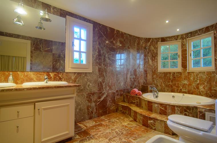 Luminous en suite bathroom with three windows