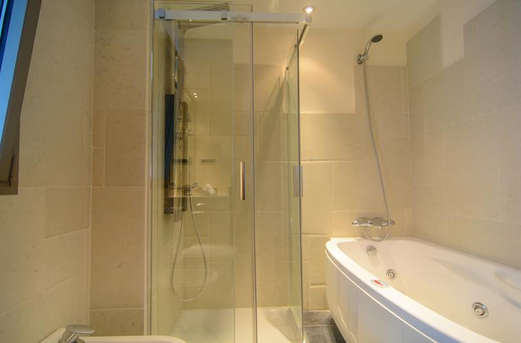 En suite bathroom with bathtub and shower cabin