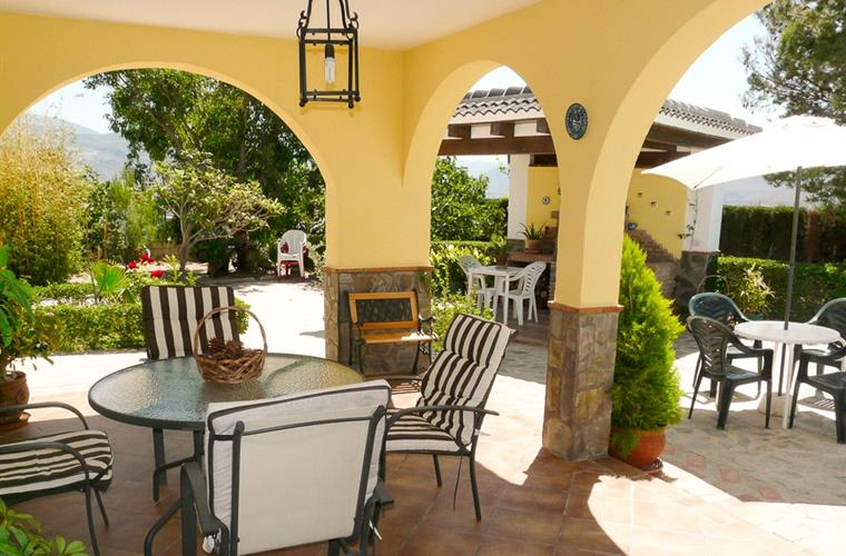 The covered terrace with comfortable garden furnitures