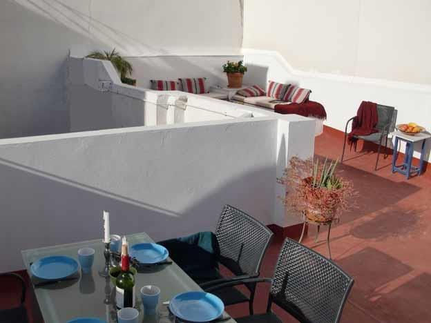 DININGTABLE AND 6 SEATS, 2 SOFAS BEHIND ON ROOF TERRASSE