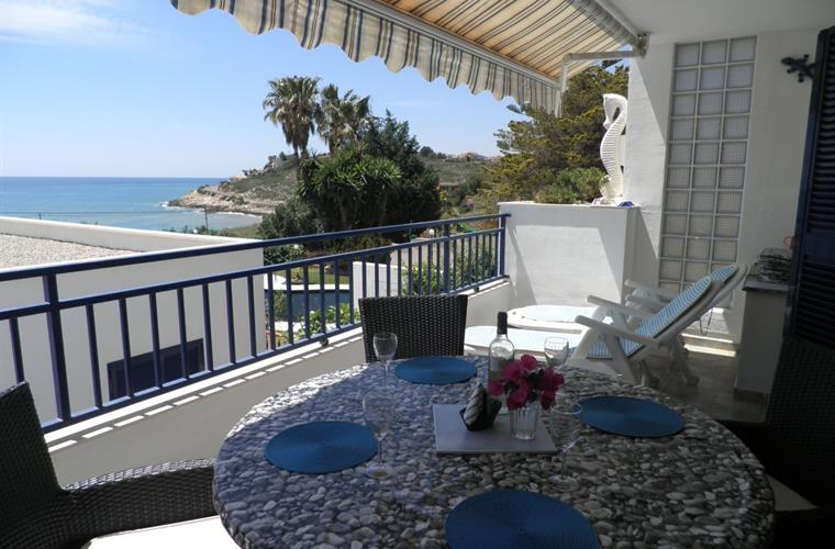 Large south facing terrace with bay view, dining table, loungers.