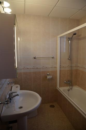 Large bathroom with a toilet, wash basin and a bath