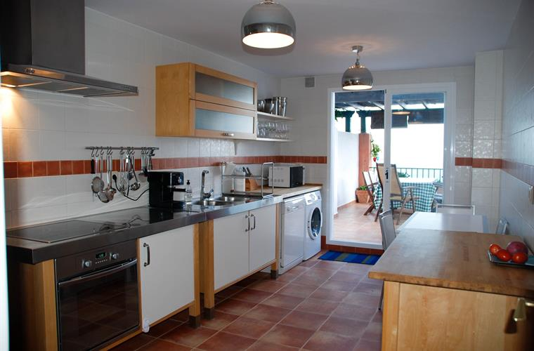 Fully equipped dining kitchen with access to outdoor dining area.