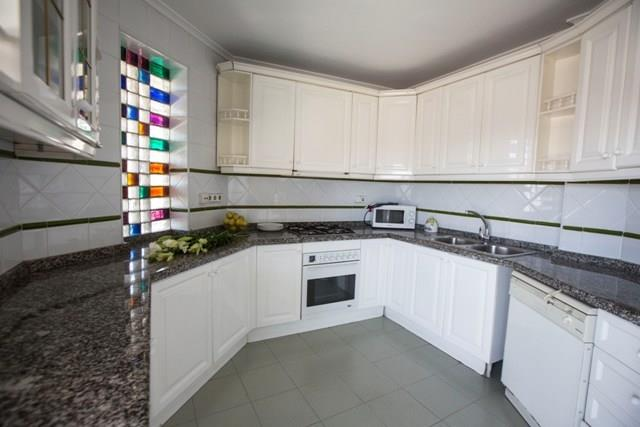 Full kitchen with coloured glass wall