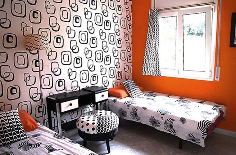 An orange and monochrome twin room in the annex.
