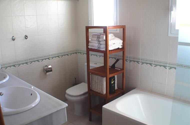 En suite bathroom with bath, twin sinks and wc