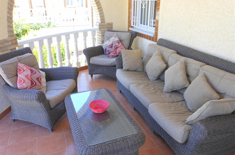 Shady terrace with comfortable sofa and chairs