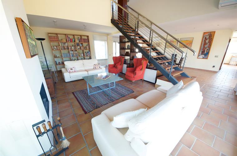LIving area of the vila with INOX stairwell leading to second floo
