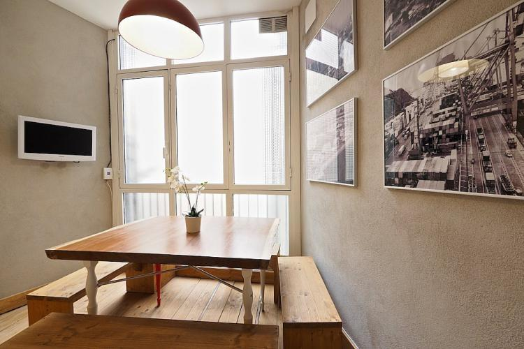 The unique dining room features a wooden table with benches and TV