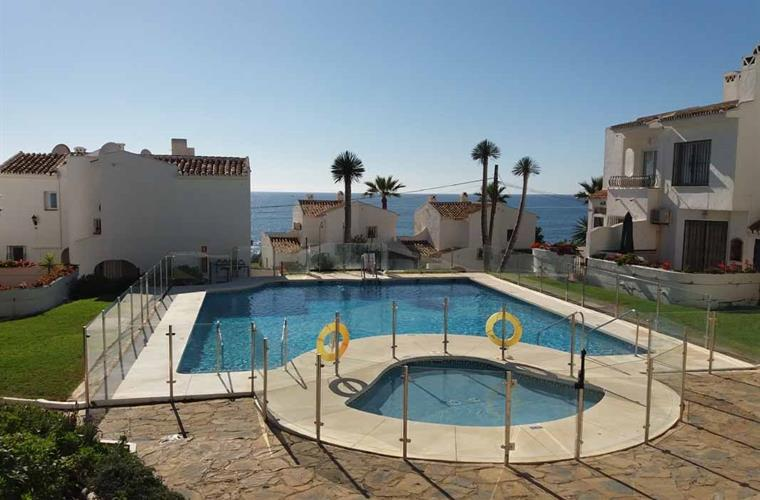 The pool area with childrens pool and sea view.