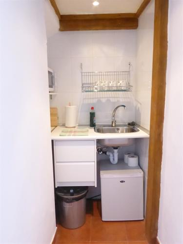 mini kitchen with fridge, microwave, toaster and kettle