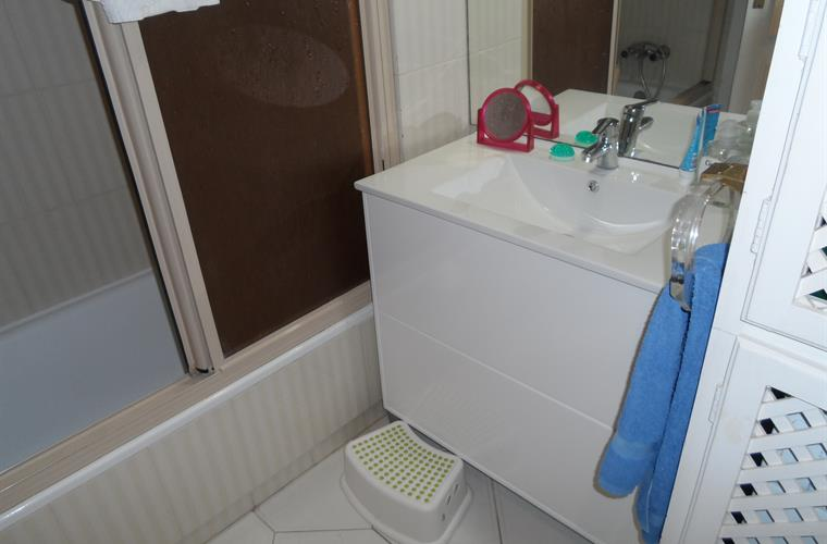 Bathroom with a tub/shower and washing machine.