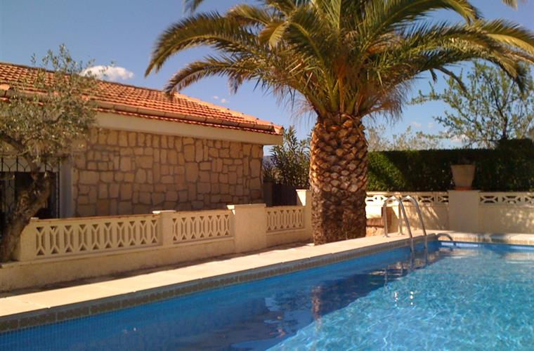 The swimming pool is situated at the side of the villa,