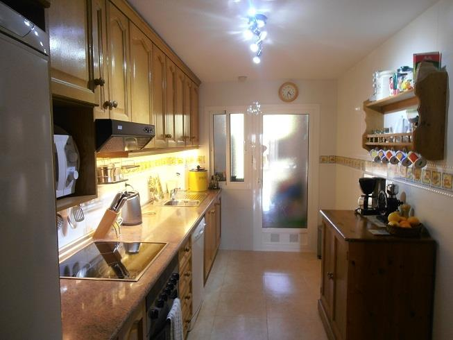 Fully equipped kitchen leading to utility room.