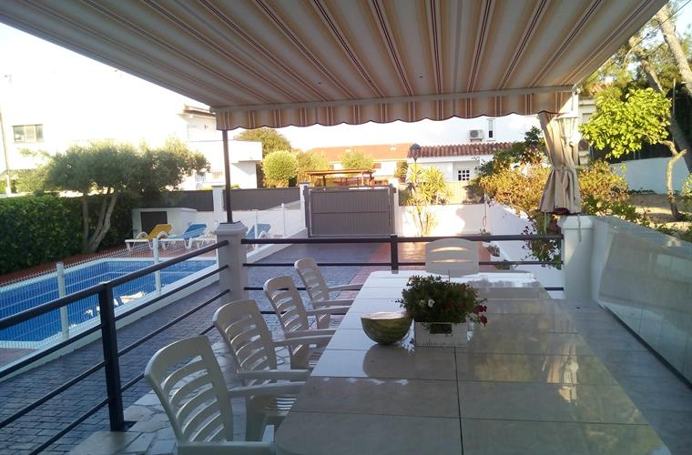Terrace with a big table for 12 people infront of the pool