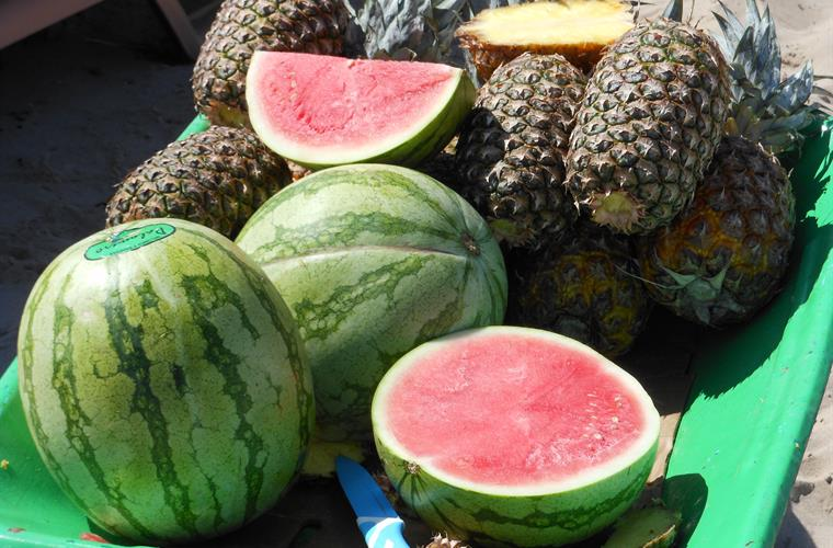 Beach seller with refreshing pineapple and watermelon