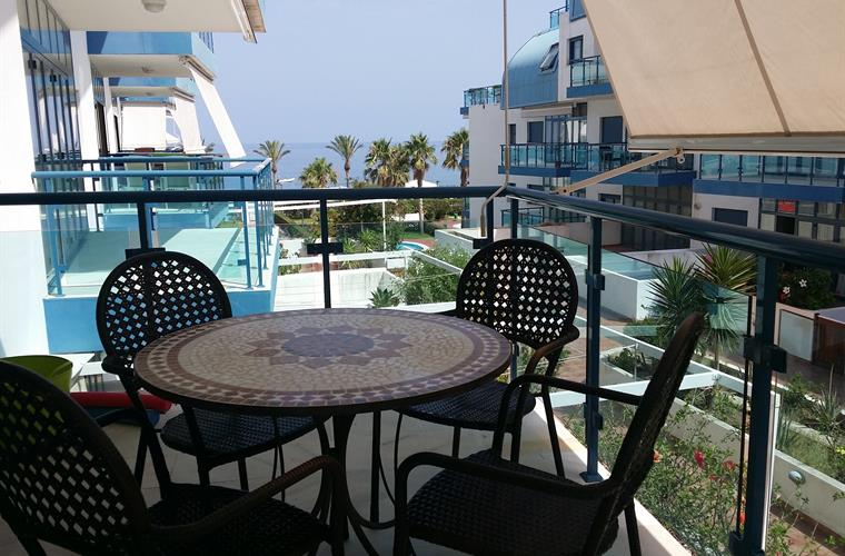 Balcony with table, chairs and a sea view