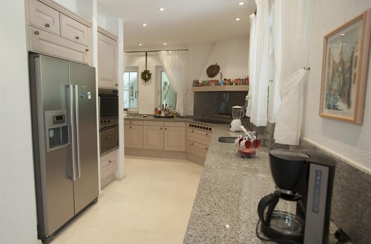 Kitchen with fridges, oven, cooking area, coffee machine, blender