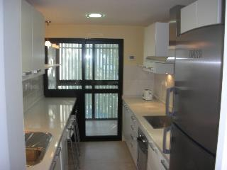 Fully equipped modern kitchen with laundry room at the back