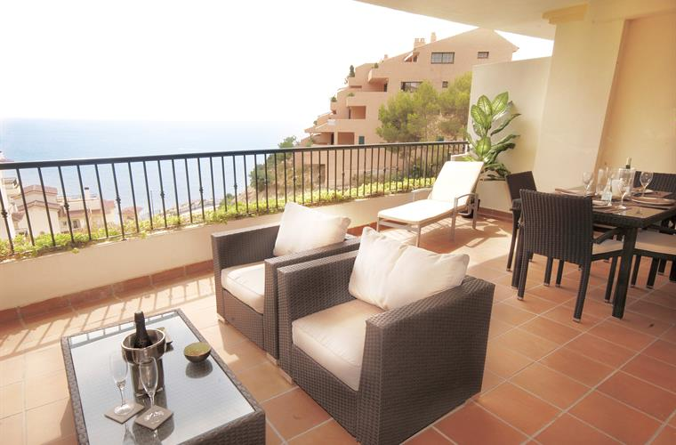 Terrace with sofas sun loungers and dining table overlooking sea
