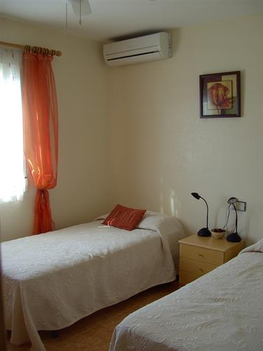back twin bedroom with free standing wardrobe. With air-con.
