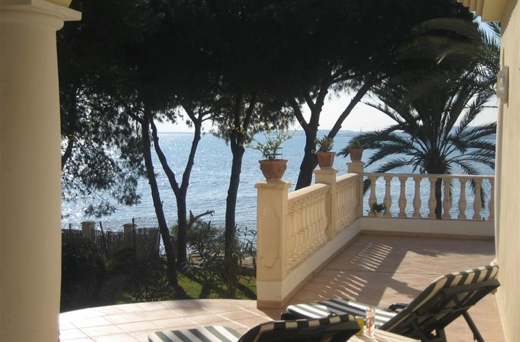 A sunny terrace with garden and sea close-by.