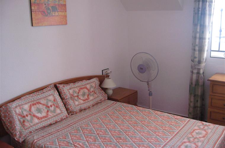 Double bedroom with wardrobe, chest of drawers, ceiling fan.