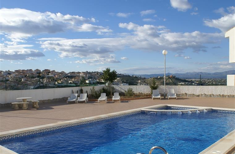 Community pool with sunbeds and view
