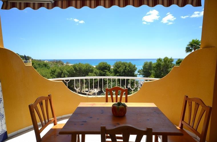 Nice balcony with sea view. Behind the trees there is a bay.