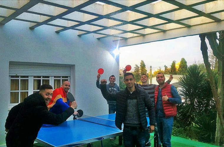 Group of guests playing table tennis in winter